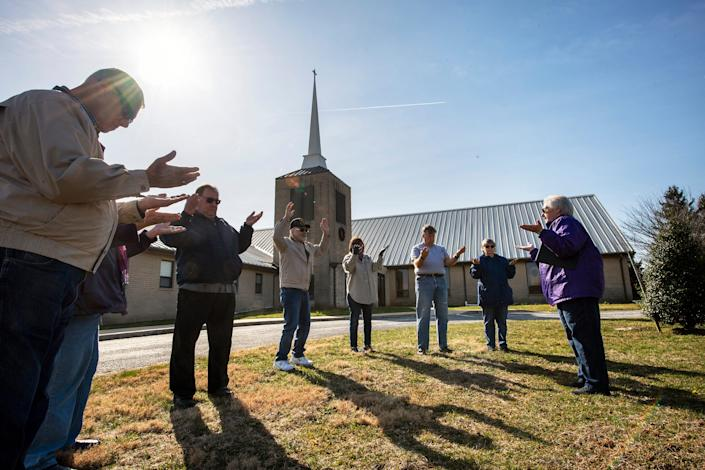 The Rev. Lou Ann Jones, right, leads prayer as eight people spread out around the flagpole at St. John's Blymire's United Church Of Christ near Dallastown, Pa., on March 16. They prayed for the community, nurses and doctors, government leaders and many others during the turmoil from the coronavirus pandemic.