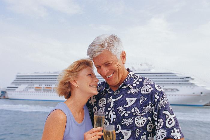 A couple smiling while sipping champagne in front of a docked cruise ship.
