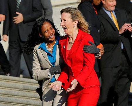 FILE PHOTO: Freshman members of the incoming U.S. 114th Congress Mia Love (R-UT) (L) and Barbara Comstock (R-VA) huddle together in freezing temperatures after participating in a class photo on the steps of the U.S. Capitol in Washington November 18, 2014.  REUTERS/Gary Cameron/File Photo