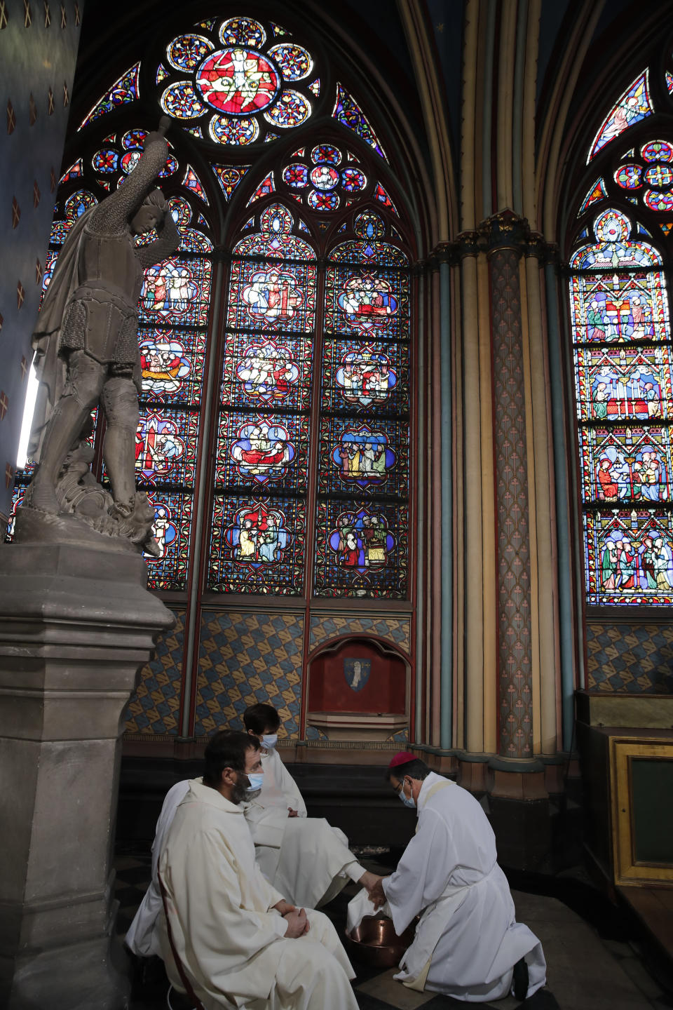 Archbishop of Paris Michel Aupetit, right, attends the Washing of the Feet ceremony for Maundy Thursday, in Notre Dame Cathedral, Thursday, April 1, 2021, almost two years after a massive fire ravaged the Gothic cathedral. (AP Photo/Christophe Ena, Pool)