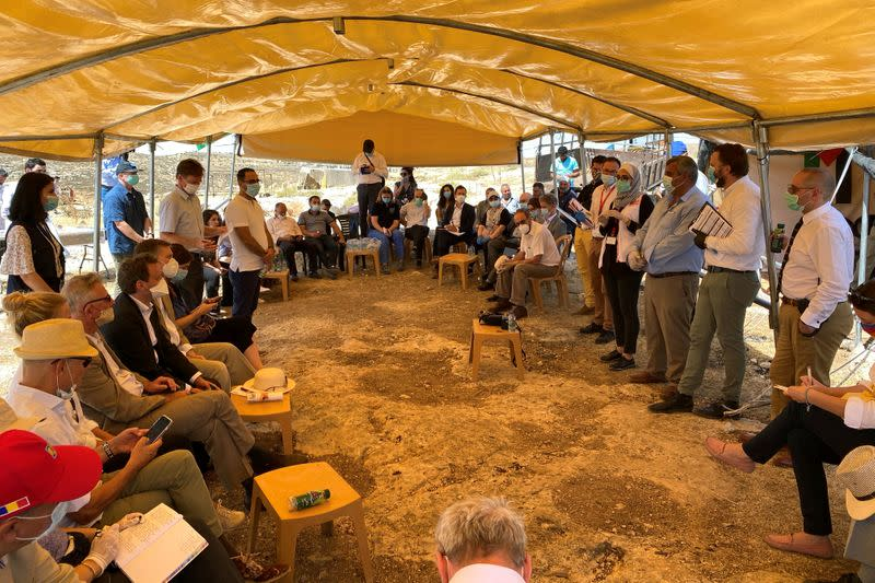 NGO workers speak to EU heads of mission and other local envoys during a diplomatic tour of Palestinian villages, near al-Mughayyir in the Israeli-occupied West Bank