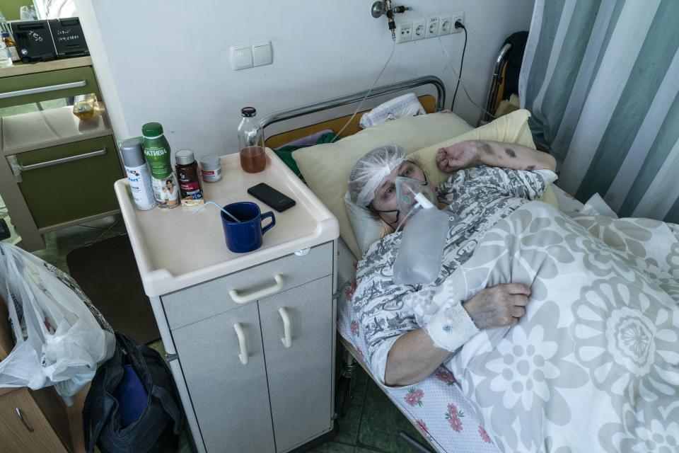An elderly woman suffering from COVID-19 breathes with the help of an oxygen mask in central district hospital of Kolomyia, western Ukraine, Tuesday, Feb. 23, 2021. After several delays, Ukraine finally received 500,000 doses of the AstraZeneca vaccine marketed under the name CoviShield, the first shipment of Covid-19 vaccine doses. The country of 40 million is one of the last in the region to begin inoculating its population. (AP Photo/Evgeniy Maloletka)