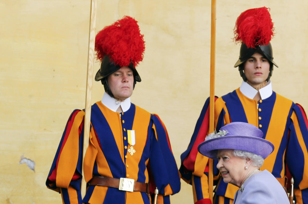 Swiss guards stand to attention as Britain's Queen Elizabeth arrives to meet Pope Francis for a meeting at the Vatican April 3, 2014. Queen Elizabeth II has come to Rome for lunch with Italy's president Giorgio Napolitano ahead of the British monarch's first meeting with Pope Francis. Before Francis, Elizabeth had met with four pontiffs, starting with Pope Pius XII in 1951, a year before her accession to the throne. (AP Photo/Stefano Rellandini, Pool)