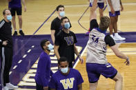 FILE - In this Tuesday, Oct. 27, 2020 file photo, Washington coaches and assistants wear masks as they watch forward Reagan Lundeen shoot during the NCAA college basketball team's practice in Seattle. For all the stops and starts endured by men's and women's college basketball teams because of the pandemic, more than 80% of scheduled conference games were played this season, according to research by The Associated Press. The season was nonetheless a grind for most teams and none had it harder than the George Washington men and UC Davis women. By Eric Olson. (AP Photo/Elaine Thompson, File)
