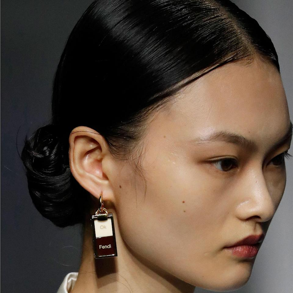 """Inspired by the rolled hairstyles of the 1930s, hairstylist Sam McKnight created low, middle-parted ponytails before rolling up the ends into tight rows of spirals for Fendi. Makeup artist Peter Philips, on the other hand, created a blurred lip look by artfully smudging the <a href=""""https://shop-links.co/1719035376308443319"""" rel=""""nofollow noopener"""" target=""""_blank"""" data-ylk=""""slk:Dior Contour Lipliner Pencil"""" class=""""link rapid-noclick-resp"""">Dior Contour Lipliner Pencil</a> in Poison Matte."""