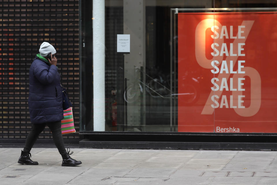 A woman walks past a Sale sign in the window of a closed shop on Oxford Street in London, Saturday, Dec. 26, 2020. London is currently in Tier 4 with all non essential retail closed and people have been asked to stay at home, on what is usually one of the busiest retail days of the year with the traditional Boxing Day sales in shops. (AP Photo/Kirsty Wigglesworth)