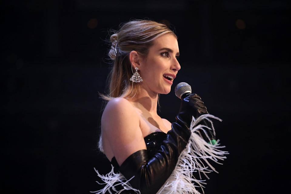 Emma Roberts speaks into a microphone onstage