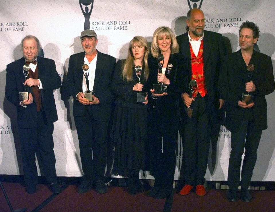 """FILE - Members of Fleetwood Mac, from left, Peter Green; John McVie; Stevie Nicks; Christine McVie; Mick Fleetwood; and Lindsey Buckingham hold their awards after the group was inducted into the Rock and Roll Hall of Fame in New York on Jan. 12, 1998. Nicks has spent the last 10 months homebound, mainly due to the coronavirus pandemic. During that time, she recorded the new single """"Show Them the Way,"""" releasing Friday and edited her new concert film """"Stevie Nicks 24 Karat Gold The Concert,"""" available at select theaters and drive-ins on Oct. 21 and 25. (AP Photo/Adam Nadel, File)"""