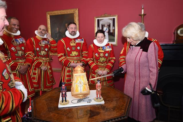 Camilla cuts into a cake she presented the Yeoman Warders at the tower. (Getty Images)