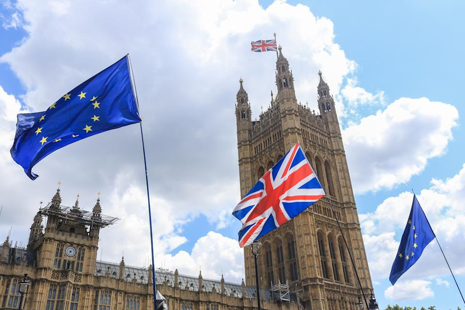 Low Angle View of British and European Union Flags Outside Parliament Buildings in London