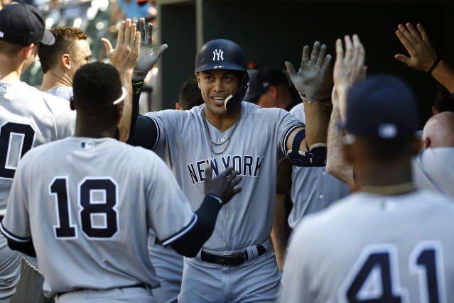 New York Yankees' Giancarlo Stanton, center, high-fives teammates in the dugout after hitting a solo home run in the second inning of the first baseball game of a doubleheader, Monday, July 9, 2018, in Baltimore. (AP Photo/Patrick Semansky)