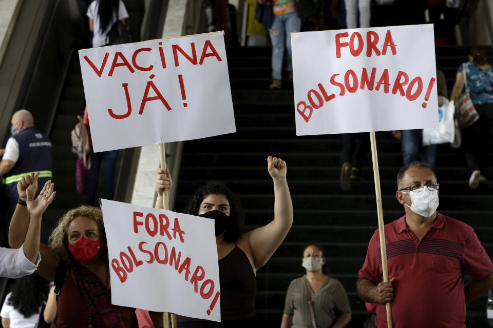 """Demonstrators hold the Portuguese messages: """"Vaccine now!"""" and """"Get out Bolsonaro"""" to protest Brazilian President Jair Bolsonaro's handling of the coronavirus, at a bus station in Brazilia, Brazil, Wednesday, Dec. 23, 2020. (AP Photo/Eraldo Peres)"""
