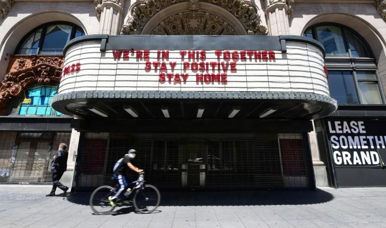 A Los Angeles cyclist in a face mask rides past the Million Dollar Theater, closed due to the coronavirus pandemic, with words on the marqee calling for togetherness