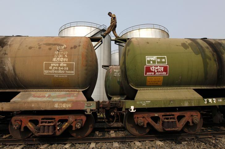 A worker walks atop a tanker wagon to check the freight level at an oil terminal on the outskirts of Kolkata November 27, 2013. REUTERS/Rupak De Chowdhuri