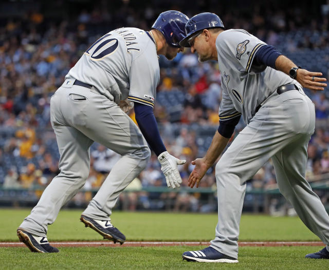 Milwaukee Brewers' Yasmani Grandal, left, is greeted by third base coach Ed Sedar after hitting a solo home run off Pittsburgh Pirates starting pitcher Joe Musgrove during the third inning of a baseball game in Pittsburgh, Thursday, May 30, 2019. (AP Photo/Gene J. Puskar)