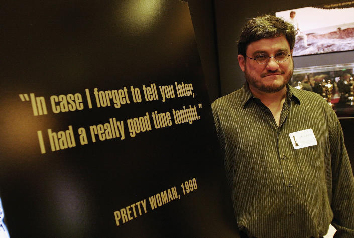"""LOS ANGELES, CA - FEBRUARY 13:  Screenwriter J.F. Lawton poses beside a poster that bears a famous line from his film """"Pretty Woman"""",  at a cocktail reception honoring the screenwriters featured in the 79th Academy Awards marketing campaign at the """"Meet the Oscars"""" exhibition space in the Hollywood & Highland complex on February 13, 2007 in Los Angeles, California.  The Academy Awards are set to occur on Sunday, February 25, 2007.  (Photo by Charley Gallay/Getty Images)"""