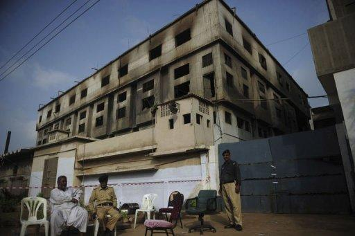 Pakistani security officials sit outside the burnt-out garment factory in Karachi