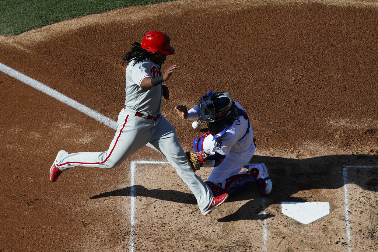 Philadelphia Phillies' Maikel Franco scores on a single by Jorge Alfaro as Los Angeles Dodgers catcher Yasmani Grandal misses the throw during the second inning of a baseball game Thursday, May 31, 2018, in Los Angeles. (AP Photo/Jae C. Hong)