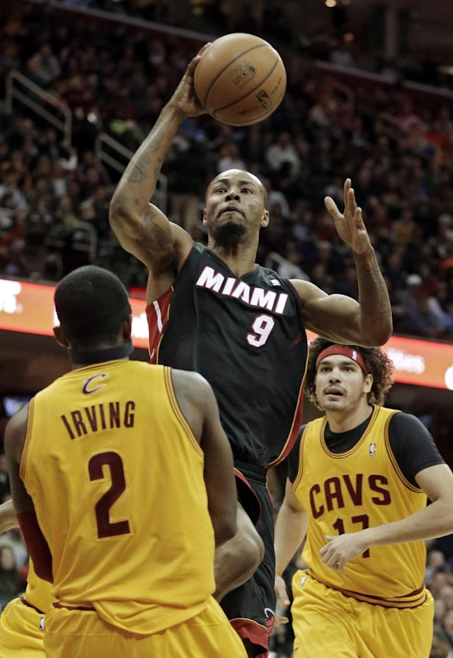 Miami Heat's Rashard Lewis (9) shoots over Cleveland Cavaliers' Kyrie Irving (2) in the first quarter of an NBA basketball game Wednesday, Nov. 27, 2013, in Cleveland. (AP Photo/Mark Duncan)