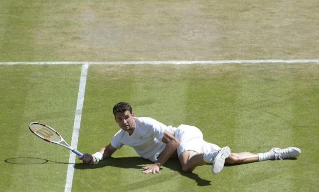 Grigor Dimitrov of Bulgaria falls to the ground as he plays against Novak Djokovic of Serbia during their men's singles semifinal match at the All England Lawn Tennis Championships at Wimbledon, London, Friday, July, 4, 2014. (AP Photo/Facundo Arrizabalaga, Pool)