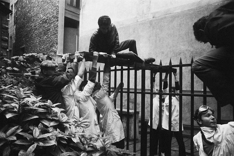 <p>A student, among the many injured during confrontations with police, is given assistance in Paris on May 6, 1968. Striking students erected the first street barricades at the Place Maubert, and then 30,000 people marched from the Place Denfert-Rochereau until they were stopped by CRS riot police. (Photo: Gökşin Sipahioğlu/SIPA) </p>