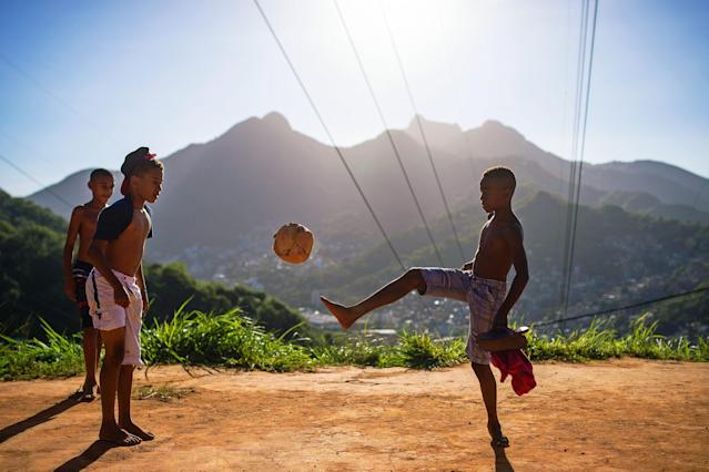 RIO DE JANEIRO, BRAZIL - NOVEMBER 02: Boys play football in the Formiga favela, or shantytown, on November 2, 2013 in Rio de Janeiro, Brazil. The favela was previously controlled by drug traffickers and is now occupied by the city's Police Pacification Unit (UPP). Football is a very popular pastime played throughout the shantytowns of Rio and all over Brazil. The UPP are patrolling Rio's favelas amid the city's efforts to improve security ahead of the 2014 FIFA World Cup and 2016 Olympic Games. (Photo by Buda Mendes/Getty Images)