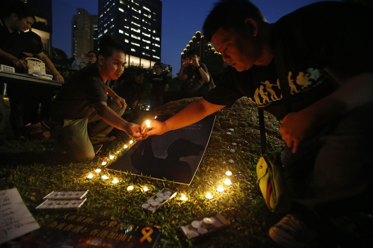 "People light candles during a candlelight vigil in solidarity with protesters of the ""Occupy Central"" movement in Hong Kong, at Hong Lim Park Speakers' Corner in Singapore October 1, 2014. REUTERS/Edgar Su (SINGAPORE - Tags: POLITICS CIVIL UNREST)"