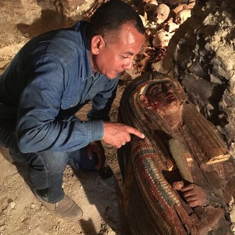 An Egyptian archaeologist looks at a newly-uncovered sarcophagus in the Draa Abul Naga necropolis - Credit: Egyptian Ministry of Antiquities via AFP