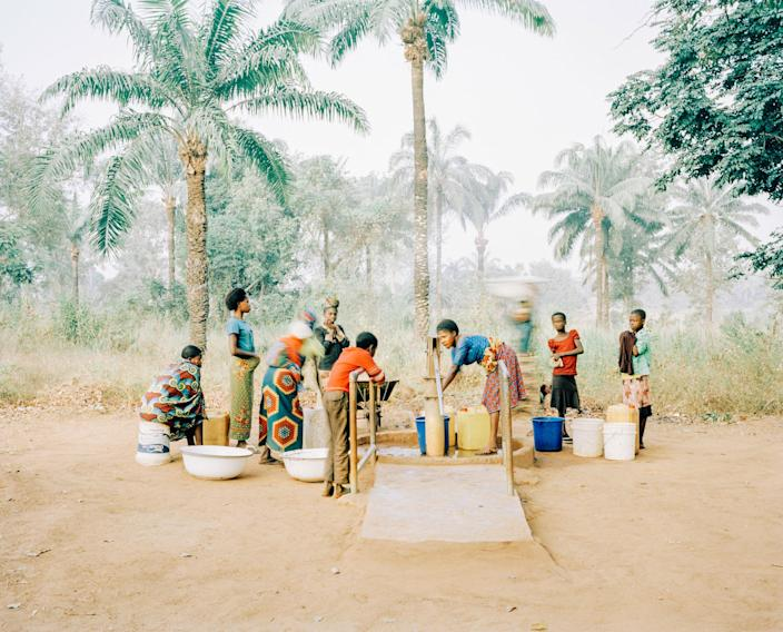 <p>Women and children gather at a hand pump in Osukputu, Benue, Nigeria, 2015. The water point serves the entire community of around 800 people with clean, safe water. For Osukputu, the arrival of clean, safe water means better health, stronger livelihoods and happier families. (Photograph by Mustafah Abdulaziz/WaterAid) </p>