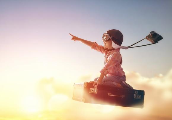 A child wearing aviator hat and goggles rides a suitcase into the sky.