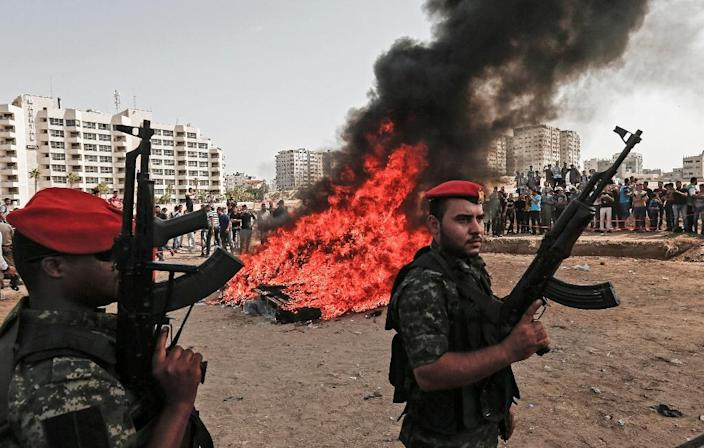 Members of Hamas's security forces in Gaza City on October 22, 2018, as confiscated drugs are set ablaze (AFP Photo/MAHMUD HAMS)