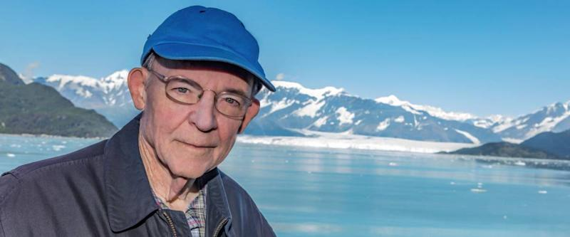 Portrait of senior man wearing blue cap with Hubbard glacier in background.