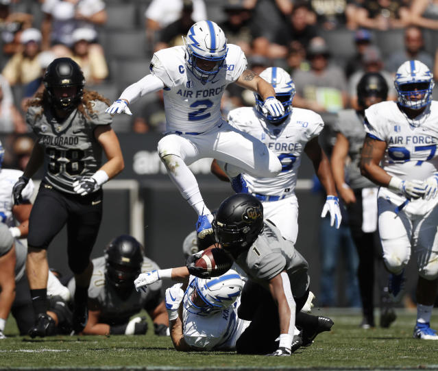Air Force defensive backs Garrett Kauppila, bottom back, and Jeremy Fejedelem pursue Colorado running back Jaren Mangham, front, as he tumbles to the turf after a short gain in the second half of an NCAA college football game Saturday, Sept. 14, 2019, in Boulder, Colo. Air Force won 30-23 in overtime. (AP Photo/David Zalubowski)