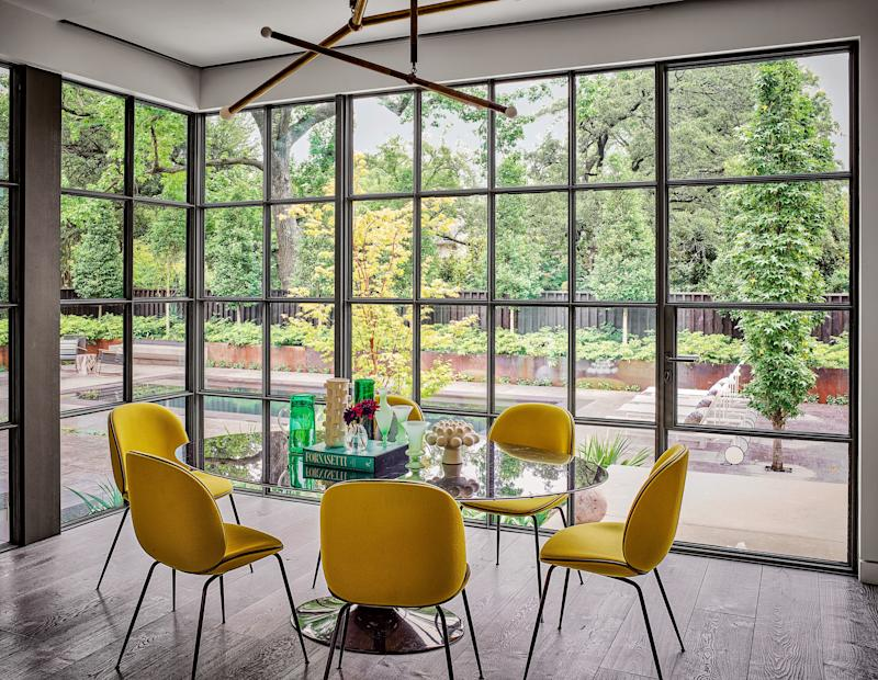 In the breakfast nook, an Apparatus chandelier is grouped with Gubi side chairs and an Eero Saarinen table from Design Within Reach.