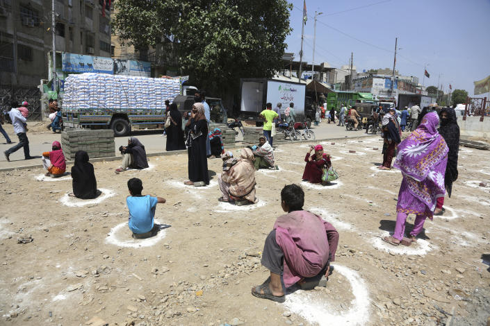 People sit at distance to receive relief goods during a nation-wide lockdown to contain outbreak of the coronavirus, in Karachi, Pakistan, Friday, March 27, 2020. The virus causes mild or moderate symptoms for most people, but for some, especially older adults and people with existing health problems, it can cause more severe illness or death. (AP Photo/Fareed Khan)