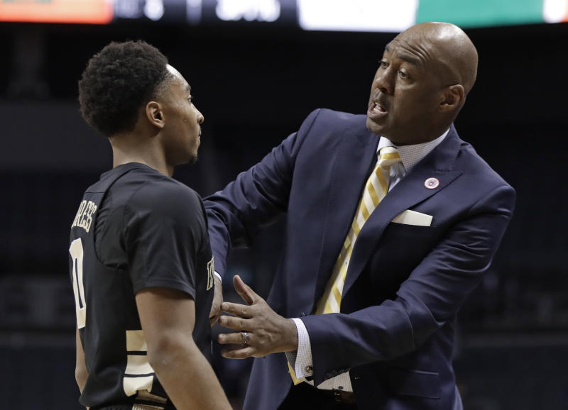 Wake Forest head coach Danny Manning, right, talks with Brandon Childress, left, during the first half of an NCAA college basketball game against Miami in the Atlantic Coast Conference tournament in Charlotte, N.C., Tuesday, March 12, 2019. (AP Photo/Chuck Burton)