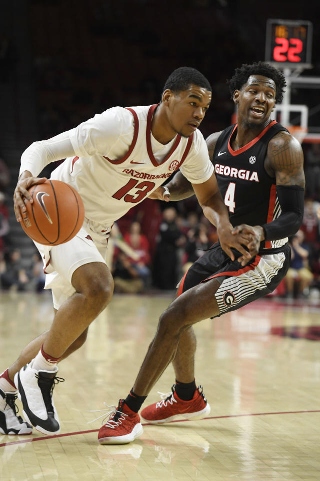 Arkansas guard Mason Jones (13) drives past Georgia defender Tyree Crump (4) during the first half of an NCAA college basketball game, Tuesday, Jan.29, 2019 in Fayetteville, Ark. (AP Photo/Michael Woods)