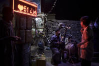 A tire repairman chats with boys as he waits for customers on the side of a road in Kabul, Afghanistan, Tuesday, Sept. 14, 2021. (AP Photo/Felipe Dana)