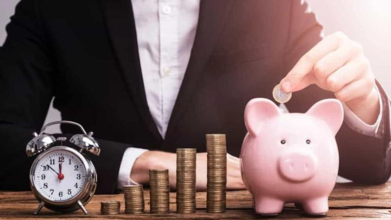 Businessperson's Hand Putting Coin In Piggybank