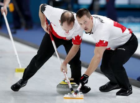 Curling - Pyeongchang 2018 Winter Olympics - Men's Bronze Medal Match - Switzerland v Canada - Gangneung Curling Center - Gangneung, South Korea - February 23, 2018 - Second Brent Laing of Canada and lead Ben Hebert of Canada sweep. REUTERS/John Sibley