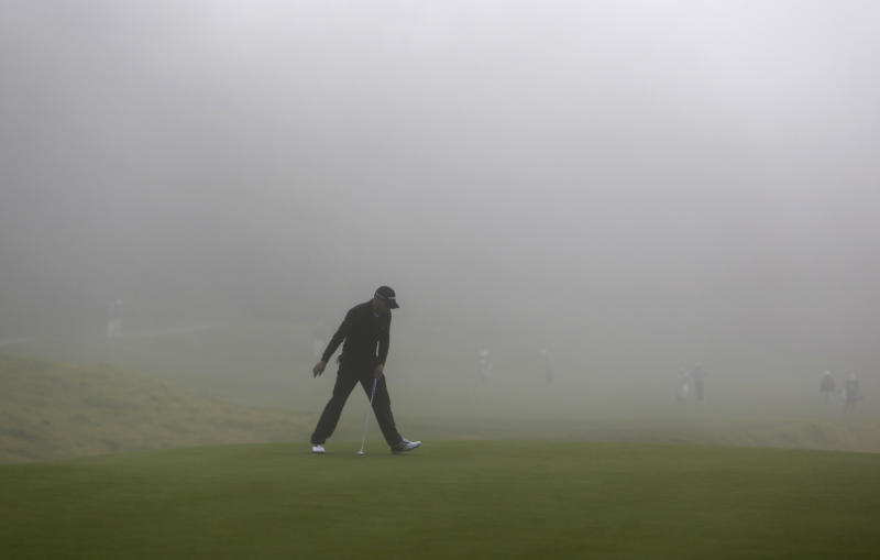 Sergio Garcia, of Spain, rolls in a birdie putt on the eighth green, as thick fog rolls in during the first round of the Northern Trust Open golf tournament at Riviera Country Club in the Pacific Palisades area of Los Angeles on Thursday, Feb. 14, 2013. (AP Photo/Reed Saxon)