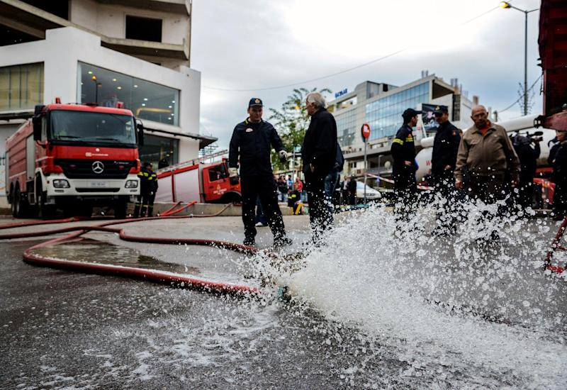 Firemen remove water from a flooded building after a heavy rain in Athens on October 25, 2014