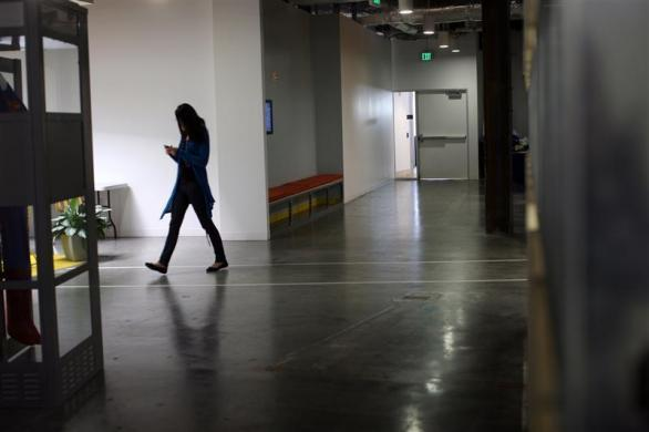 An employee walks near a telephone booth for private cell phone discussions at the new headquarters of Facebook in Menlo Park, California January 11, 2012.