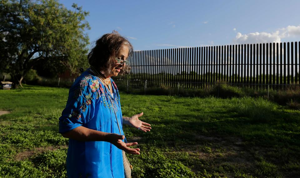 In this Sept. 17, 2015, photo, Dr. Eloisa Tamez walks in her backyard where the border fence passes through her property, in San Benito, Texas in the Rio Grande Valley. Tamez refused to cede her three acres in San Benito for the building of the wall, land that had been in her family for generations. A federal judge ruled in the government's favor, and Tamez was compensated $56,000. With the looming prospect of a long and drawn-out fight over a proposed U.S.-Mexico border wall, government lawyers are taking new action to close the last cases against landowners over the existing border fence. (AP Photo/Eric Gay)