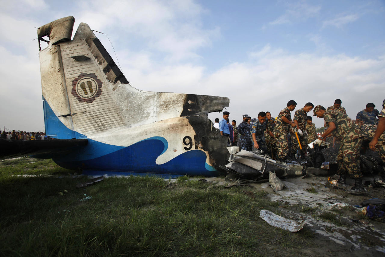 Nepalese police search through the debris at the crash site of a Sita Air airplane near Katmandu, Nepal, early Friday, Sept. 28, 2012. The plane carrying trekkers into the Everest region crashed just after takeoff Friday morning in Nepal's capital, killing all 19 people on board, authorities said. (AP Photo/Niranjan Shrestha)