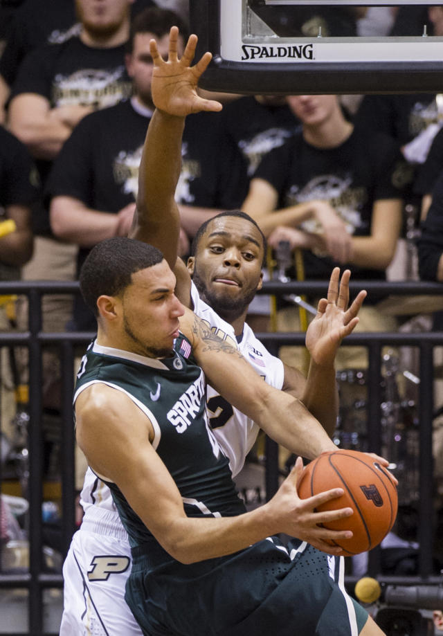 Purdue's Errick Peck (32) goes up in an attempt to block the shot of Michigan State's Denzel Valentine (45) in the second half of an NCAA college basketball game, Thursday, Feb. 20, 2014, in West Lafayette, Ind. Michigan State defeated Purdue 94-79. (AP Photo/Doug McSchooler)