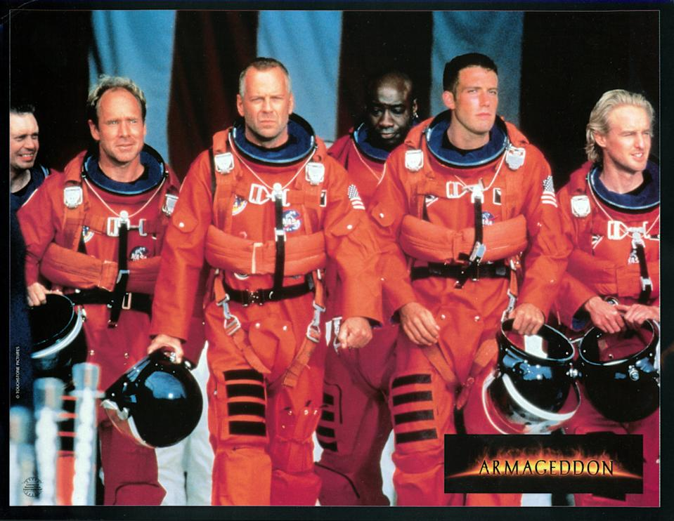 Steve Buscemi, Will Patton, Bruce Willis, Michael Clarke Duncan, Ben Affleck, and Owen Wilson walking in NASA uniforms in a scene from the film 'Armageddon', 1998. (Photo by Touchstone/Getty Images)