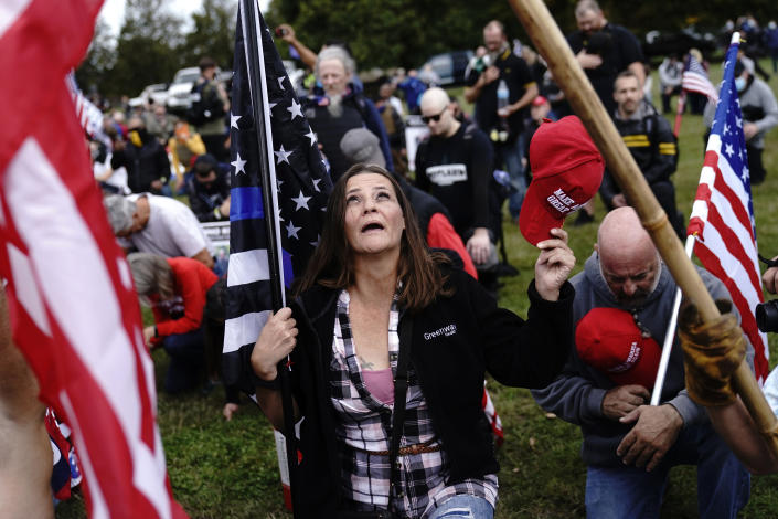 Members of the Proud Boys and other right-wing demonstrators kneel in prayer at a rally on Saturday, Sept. 26, 2020, in Portland, Ore. (AP Photo/John Locher)