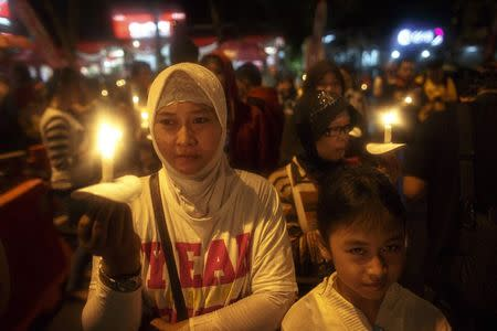 Indonesians hold up candles during a candle light vigil for the victims of AirAsia flight QZ8501 at Surabaya December 31, 2014. REUTERS/Athit Perawongmetha