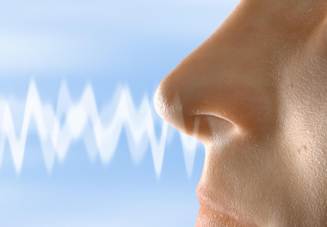 Close up visualization of a smell moving towards a human nose.
